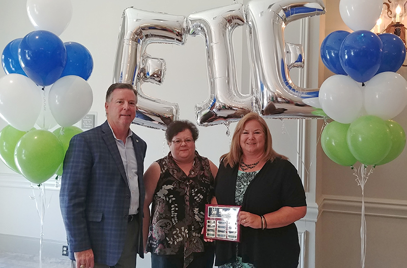 Three people in business dress surrounded by green, white and blue and silver balloons, one of them holding a plaque.