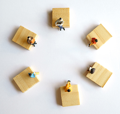 Model figures on wood planks visualizing the concept of social distancing..